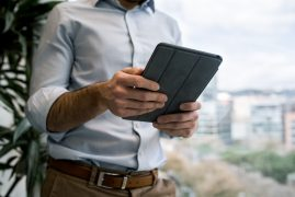 A man uses a tablet. He is feeling happy after starting counseling for men in Boulder, CO with North Boulder Counseling.