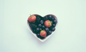 A heart-shaped bowl of berries on an empty table is shown. This reflects concepts discussed in eating disorder treatment in Boulder, CO with North Boulder Counseling.