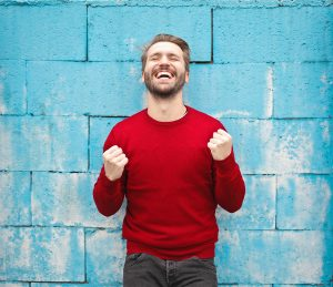man in a red sweater smiles and feels relieved after anxiety treatment in boulder, co with an anxiety therapist at North Boulder Counseling 80301. Online therapy in Colorado can also help you with an online therapist for anxiety treatment.