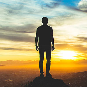 A person stands looking into the sunset. They are feeling happier since beginning mindfulness-based therapy in Boulder, CO with North Boulder Counseling 80301.