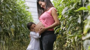 pregnant mother with her son kissing her stomach. She gets postpartum anxiety counseling in boulder, co for postpartum anxiety and OCD at North Boulder Counseling 80301