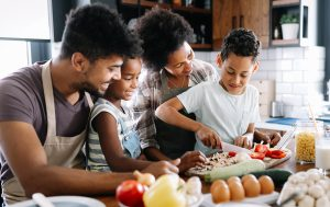 A family stands in the kitchen cooking together. They are feeling happy after starting parent coaching in Boulder, CO for blended families with North Boulder Counseling.