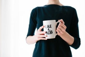 "A woman holds a coffee cup that reads ""like a boss."" This reflects concepts discussed in clinical supervision in Boulder, CO with North Boulder Counseling 80301."