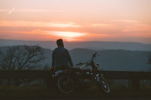 Photo of man looking at the Colorado Rockies next to his motorcycle representing how therapy can give you the freedom to live your life to the fullest!
