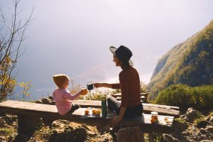 Photo of mother and daughter having a tea party on a hike representing an adult mindfully playing after conquering their own fears with help from a therapist.