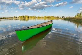 green canoe on a calm lake in a fisheye perspective, late summer in Arapaho Bend Natural Area, Fort Collins, Colorado representing how working on therapy during the summer can give you the space to explore the things you enjoy even more.