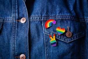 Pride pins on a denim jacket representing being an LGBTQ ally. Boulder Therapists who offer LGBTQ counseling in Boulder, CO discuss ways you can be a good ally all year long