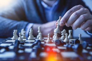 A person moves a chess piece as the opposing pieces lay scattered. This could represent a strong strategy developed from business coaching for therapists in Boulder, CO. Contact a business coach to learn more about private practice business coaching in Boulder, CO and other services.