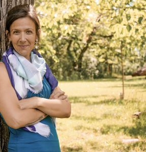 Gen smiles as she poses against a tree in an open park. She is a business coach in Boulder, CO that offers private practice business coaching for therapists. Contact North Boulder Counseling for more information today!